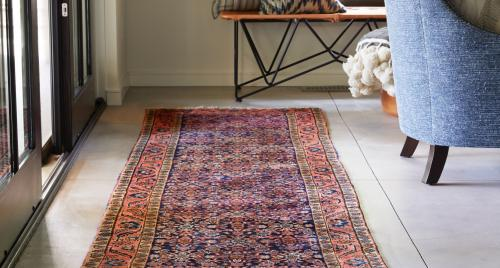 Vintage rug between sliding doors and a chair